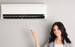 professional-woman-controlling-air-conditioning-unit-with-remote-handset